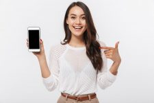 Girl in white shirt pointing at phone