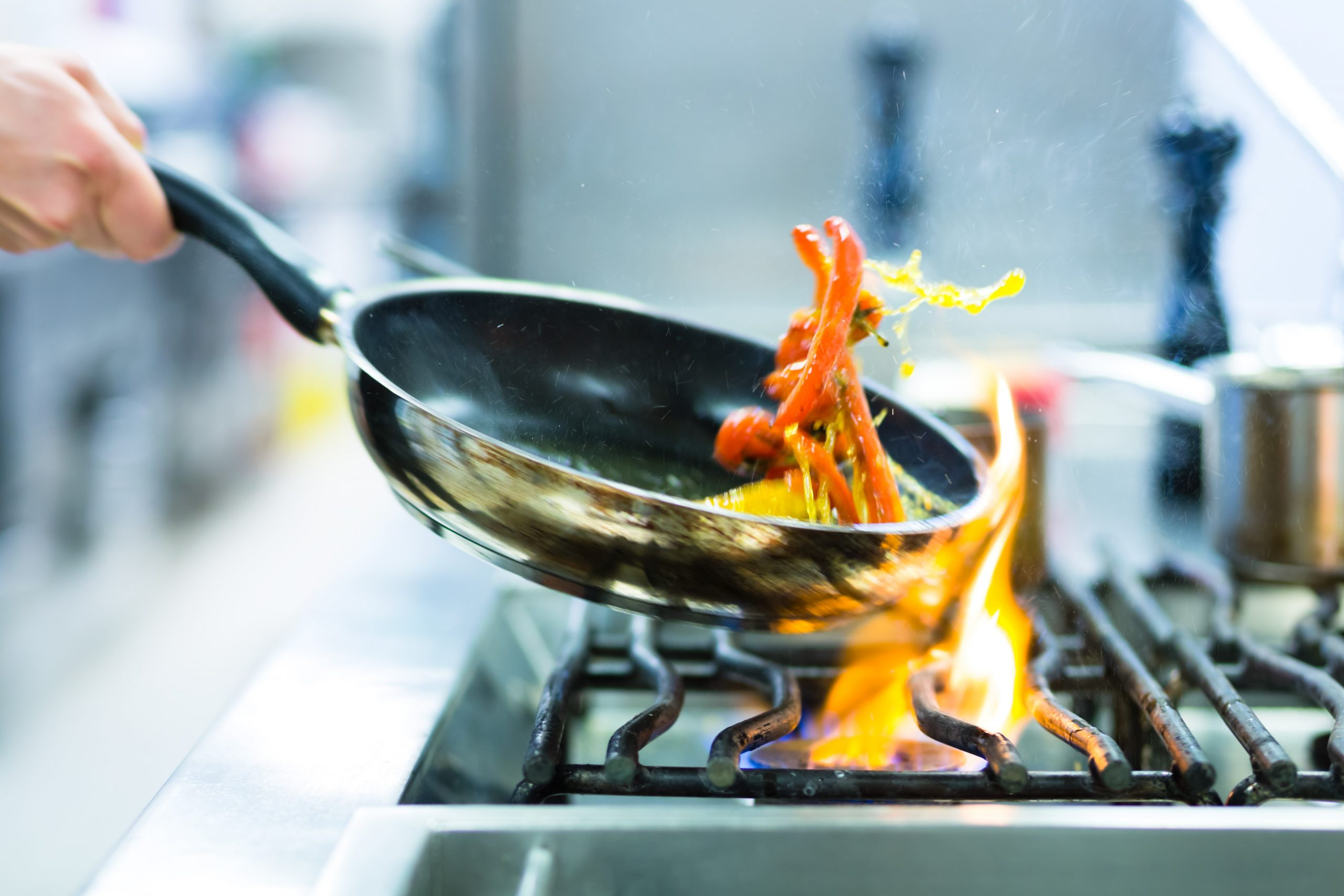 Cooking food over a stove flame