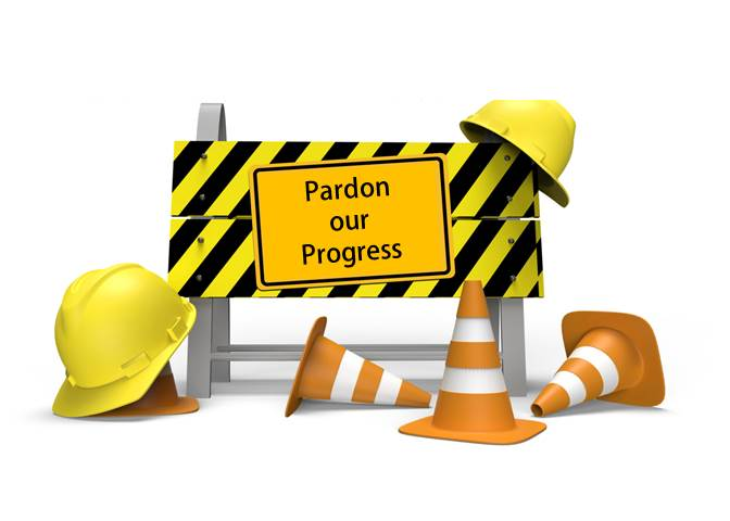 Pardon Our Progress construction sigh with hard hats and safety cones