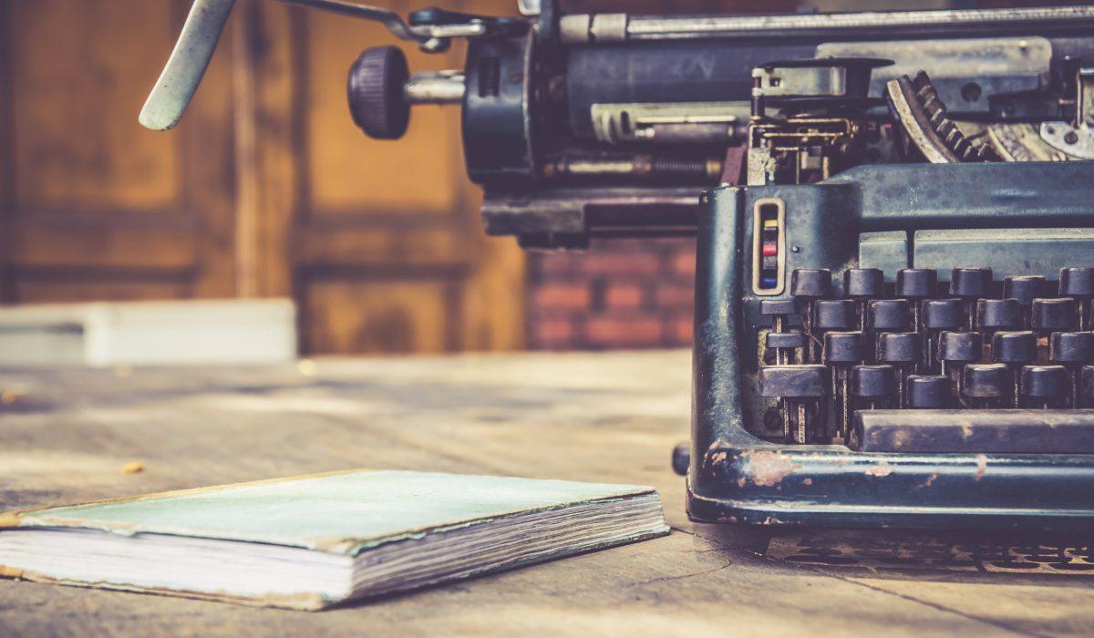 Old typewriter sitting next to old notebook